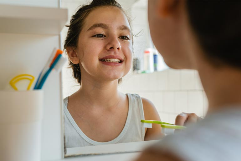 girl doing dental checkups in mirror