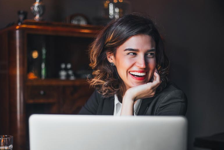 woman smiles with veneers while working